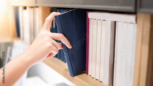 Fotografie, Obraz Male hand choosing and picking blue book from wooden bookshelf in public library