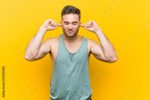Young fitness man against a yellow background covering ears with hands. - 270051282