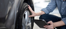 Asian Auto Mechanic Holding Digital Tablet Checking Car Wheel In Auto Service Garage. Mechanical Maintenance Engineer Working In Automotive Industry. Automobile Servicing And Repair Concept