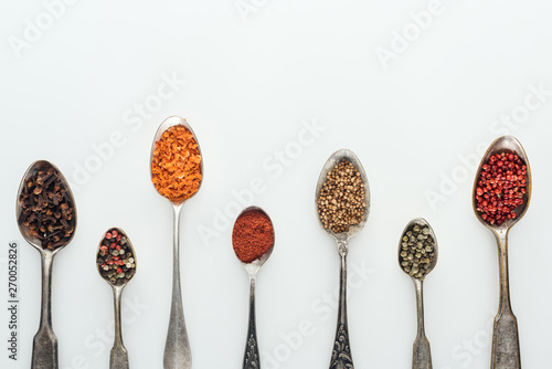 Fototapeta top view of colorful spices in silver spoons on white background with copy space obraz