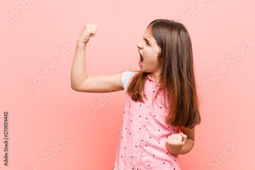 Fotografiet  Cute little girl raising fist after a victory, winner concept.