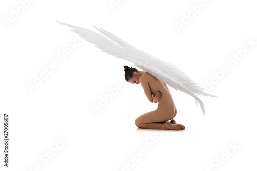 Photo  Nude angel with white wings embracing body