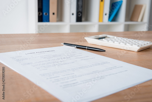 loan agreement, pen and calculator on wooden table in office