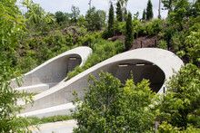 Attractive Tunnels Over Highway In Tulsa Oklahoma Near Park And Arkansas River With Many Young Trees Supported As They Grow And Wildflowers Blooming Beside Road