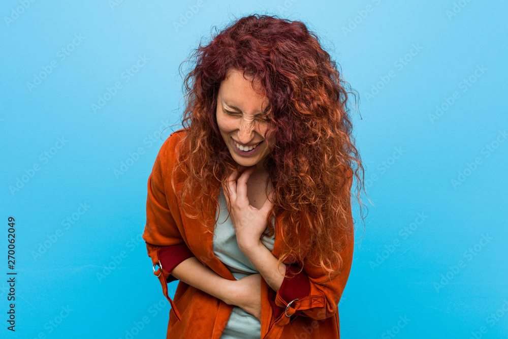 Fototapety, obrazy: Young redhead elegant woman laughs happily and has fun keeping hands on stomach.