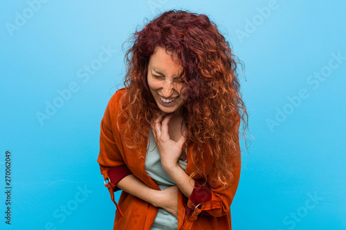 Fényképezés  Young redhead elegant woman laughs happily and has fun keeping hands on stomach