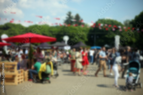 Tablou Canvas Defocused background of people in park food festival, summer festival, sunny day