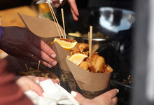 Street Food Festival. Picture Of Fish And Chips With Hands Of Event Guests.