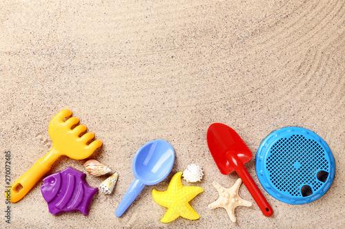 Colorful plastic toys and seashells on beach sand Canvas Print