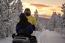 2 People Riding On A Snowmobile Through The Wilds Of Lapland