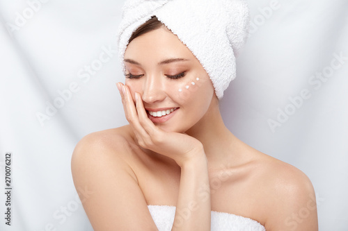 Fototapeta cute girl in bath towel and cream on the cheek looking down with smile, young happy woman moisturizing her face obraz na płótnie