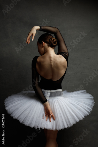 Young beautiful ballerina is posing in studio Wallpaper Mural
