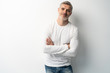 canvas print picture - Cheerful man of middle age against white background, wearing jeans and white T-shirt, mid shot.