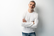 Cheerful Man Of Middle Age Against White Background, Wearing Jeans And White T-shirt, Mid Shot.