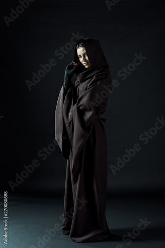 Fotografie, Tablou  full length view of woman in death costume holding dice on black
