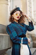 Fashionable Curly Woman Wearing Trendy Leather Beret, Cat Eye Sunglasses, Checkered Blue Dress, Holding White Faux Leather Bag, Model Posing In Street Of European City