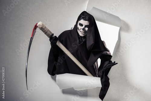 woman in death costume holding scythe and getting out of hole in paper Tablou Canvas