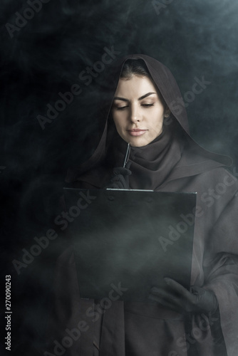 woman in death costume holding clipboard on black Fototapet