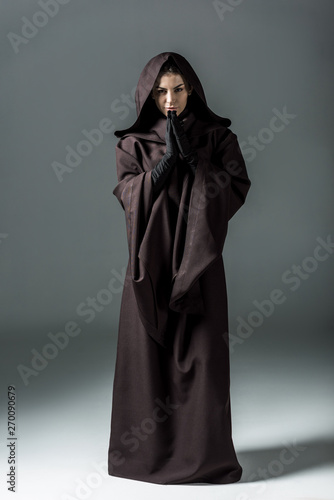 Fotografie, Tablou full length view of smiling woman in death costume showing please gesture on gre