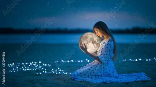 Photo  Beautiful attractive girl on a night beach with sand and stars hugs the moon, Ar