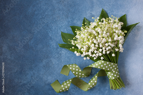 Valokuva Lily of the valley bouquet on blue gradient background decorative plaster