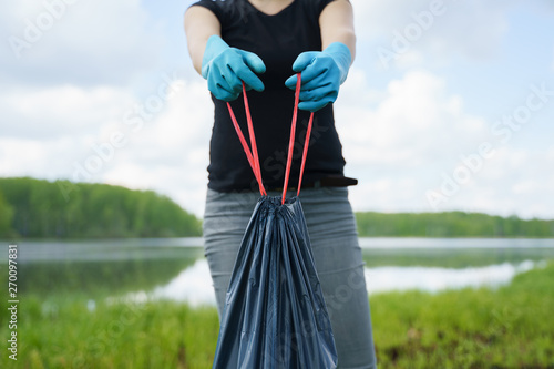 Photo of woman in rubber gloves with full garbage bag on river bank Canvas-taulu