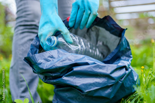 Valokuva  Photo of girl in rubber gloves picking up dirty plastic bottle in bag on green l