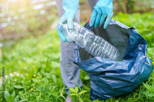 Photo of human in rubber gloves picking up dirty plastic bottle in bag on green Canvas-taulu
