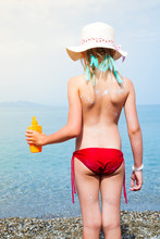 Little Adorable Girl With White Hat And Blue Hair Hold Suncream Bottle On The Sea Beach. Summer Vacation In Aegean Sea, Kos Island Greece