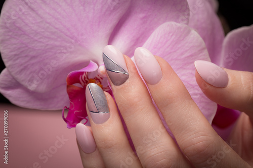 purple-neat-manicure-on-female-hands-on-flowers-background-nail-design