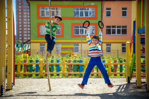 Poster Havana Two brothers sibling boy in casual clothes on playground climbing rope and athletic rings. Kids has a lot of fun. Healthy leisure time with children. Family competition friendship concept