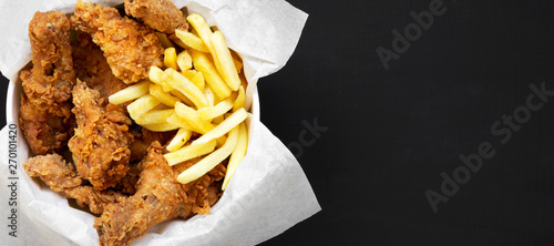 Fototapeta Tasty fastfood: fried chicken legs, spicy wings, French fries and chicken stips in paper box over black background, top view. Flat lay, overhead, from above. Copy space. obraz