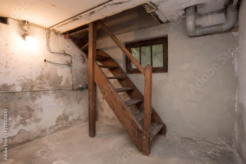 empty basement in abandoned old industrial building with little light and a wood Canvas Print