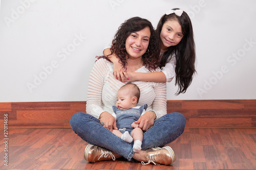 mom with her cute baby in her arms and her eldest daughter hugs her from behind Wallpaper Mural