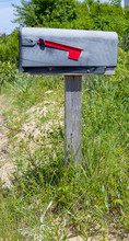 Rural Mailbox On Post With Red Flag Down.