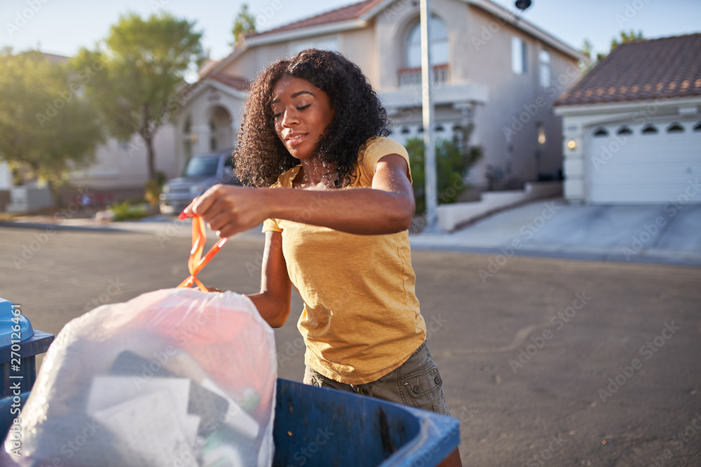 Fototapeta african american woman taking out the tash in las vegas neighborhood,