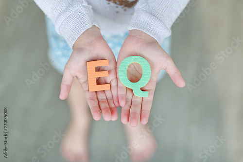 Valokuva  EQ (Emotional Quotient) sponge text on child hands