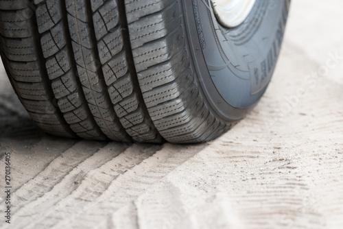 Fényképezés  Ein Reifen und Reifenspuren im Sand