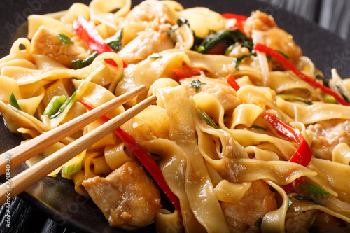 Fotografija  Drunken noodles pad kee mao with chicken, basil, chili pepper and sauce close-up on a plate