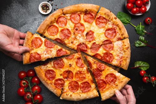 Fotografie, Obraz  Pepperoni pizza on black concrete background top view