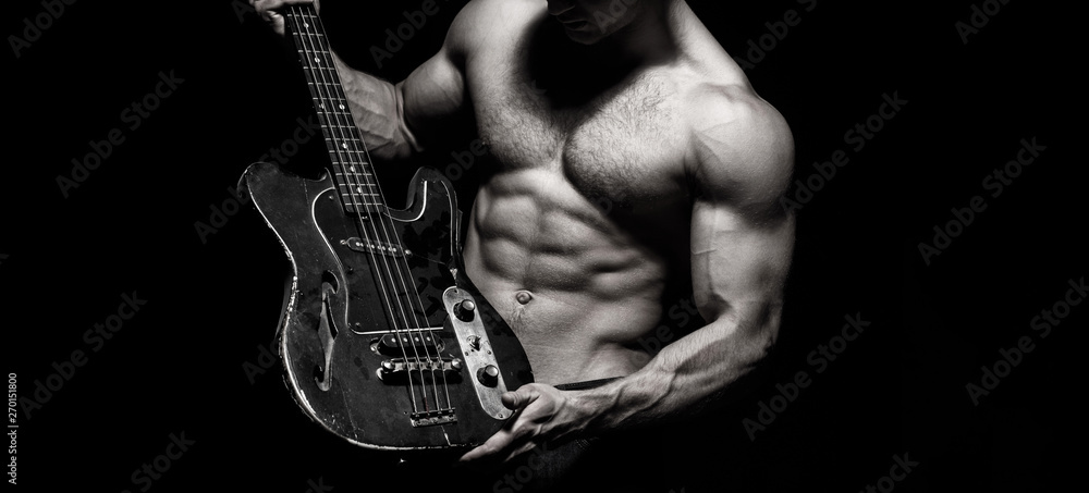 Chest muscles, Six pack, ab, triceps. Music festival. Instrument on stage and band. Strong, muscular, muscles man, bodybuilding. Guitar. Torso man. Play the guitar. Music concept. Electric guitar.