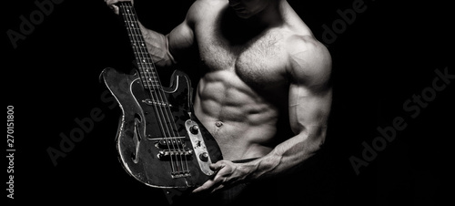 Chest muscles, Six pack, ab, triceps. Music festival. Instrument on stage and band. Strong, muscular, muscles man, bodybuilding. Guitar. Torso man. Play the guitar. Music concept. Electric guitar. - 270151800