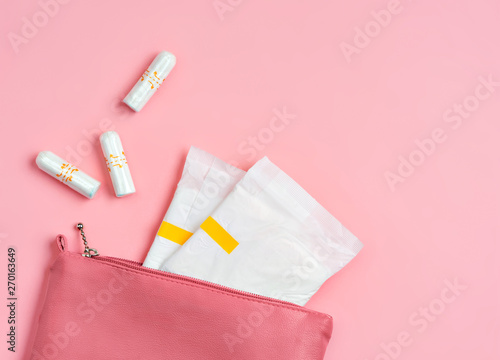 Sanitary pads and tampons in cosmetic bag on pink background Wallpaper Mural