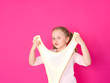 canvas print picture - girl is playing with yellow slime in front of pink background