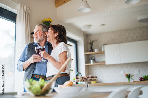 A senior couple with wine indoors at home, looking out of window.