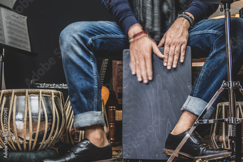 A stylish musician in denim and double monk shoes plays the Cajon, a Peruvian drum used commonly with Spain's Flamenco dance.  - 270185045