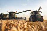 Fototapeta Miasto - Mähdrescher und Traktor bei der Ernte auf einem Weizenfeld