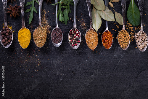 Canvas Prints Spices Spices and herbs on spoons in a black background, top view. Indian cuisine.