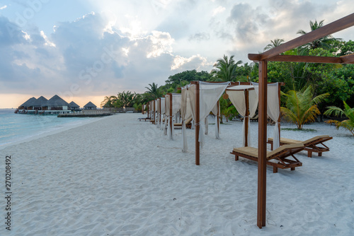 beach view with loungers, water villas and palmes Fototapet
