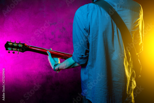 Close-up photo of hipster man with red guitar in neon lights. Rock musician is playing electrical guitar. - 270209616